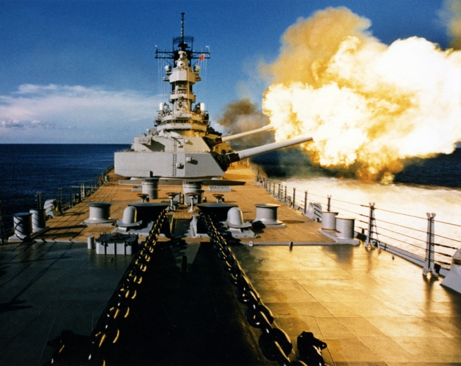 Wisconsin firing a broadside to port with her 16-inch/50 and 5-inch/38 guns, circa 1988-91. (Naval History and Heritage Command Photograph NH 97207-KN).