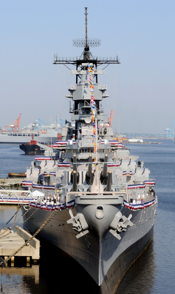 The decommissioned Wisconsin berthed at Nauticus during a ceremony officially transferring the battleship from the Navy to the city of Norfolk, 16 April 2010. The transfer ended the requirement for the ship to be preserved for possible recall to active duty. (Mass Communication Specialist Seaman Scott Pittman, U.S. Navy Photograph 100416-N-3154P-001, Navy.mil Photos).