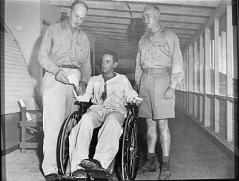 CDR Eugene Own examines dressings of Dr. Haynes at Naval Hospital Guam. CAPT McVay stand at right--BUMED Archives