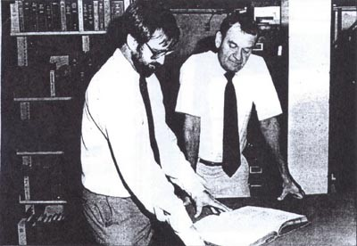 """Inside the stacks, John Vajda (right) assistant librarian (later Library Director] and Dale Sharrick, circulation librarian, peruse an 18th century manuscript. The rare book collection is part of the 200,000 volume Navy Department Library, established in 1800 by order of Pres. John Adams. It includes cruise books and rare administrative records."