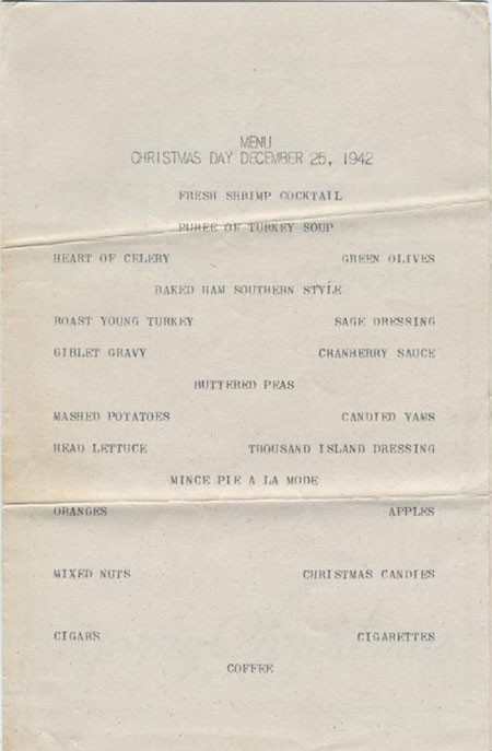 Menu Christmas Day December 25, 1942. Fresh Shrimp Cocktail, Puree of Turkey Soup, Heart of Celery, Green Olives, Baked Ham Southern Style, Roast Young Turkey, Sage Dressing, Giblet Gravy, Cranberry Sauce, Buttered Peas, Mashed Potatoes, Candied Yams, Head Lettuce, Thousand Island Dressing, Mince Pie a la Mode, Oranges, Apples, Mixed Nuts, Christmas Candies, Cigars, Cigarettes, Coffee.