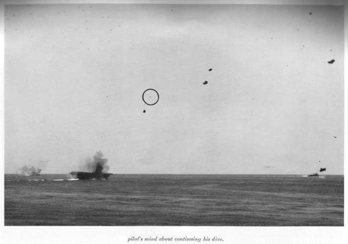 "Japanese plane turning away after having started dive on carrier. Large black bursts are 5"" shells, and close bursts probably changed pilots mind about continuing his dive."