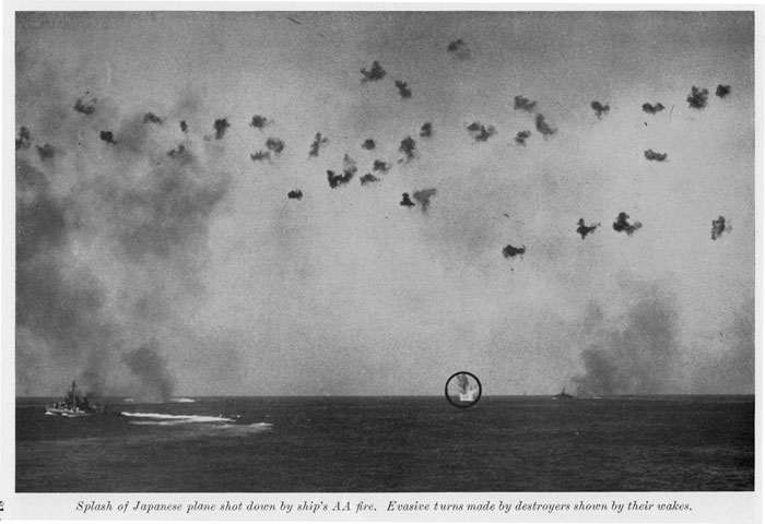 The above photograph illustrates a good safe distance to keep enemy planes. Japanese plane about to crash in the sea after being shot down. Smoke from destroyers is caused by firing of guns, and wakes show turn maneuvers executed by the formation during firing. Note number of AA bursts.