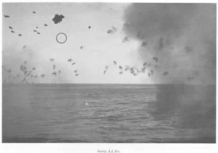 "Another illustration of a good safe distance to keep enemy planes. Japanese plane (believed ""Zeke"") approaching formation under heavy AA fire."