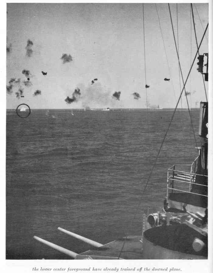 Splash of Japanese plane seen in two preceding photos taken a few seconds earlier. AA guns in the lower center foreground have already trained off the downed plane.