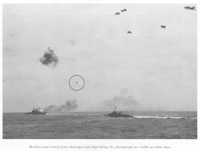 "Japanese fighter plant (""Zeke"") continuing the dive on cruiser. Flame and smoke from cruiser caused by firing of AA batteries. Machine-gun tracers from destroyer and ship taking the photograph are visible as white dots."