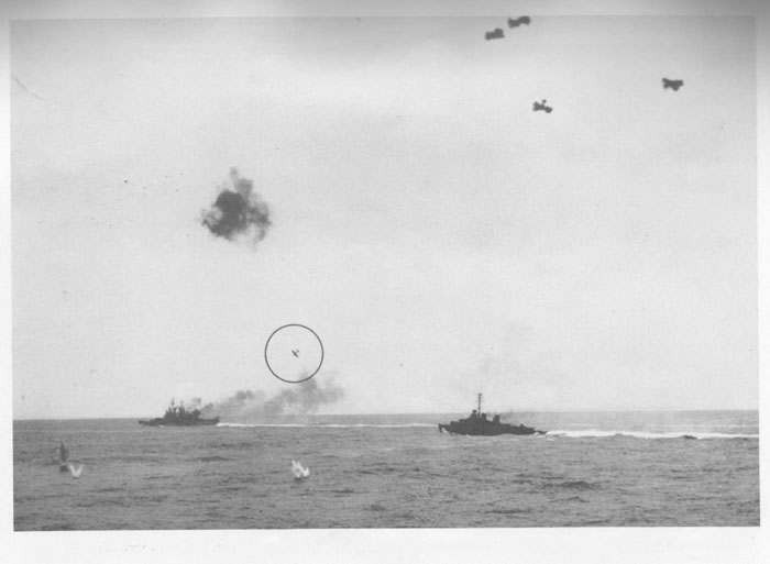 "Japanese fighter plane (""Zeke"") continuing dive on cruiser which is trailing smoke from fire of her own AA batteries."