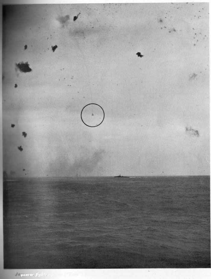 "Japanese fighter plane (""Zeke"") falling in flames near destroyer. AA fire is accurate."