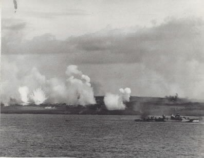 "Iwo Jima Operation, 1945: White phosphorous rounds burst ashore as destroyers prepare for a underwater demolition team operation off Iwo Jima's West Beach at 4:00 P.M., 17 February 1945. Note ""Fletcher"" class destroyer firing at right. Photographed from USS Texas (BB-35). NHHC Photographic Section #80-G-309163."