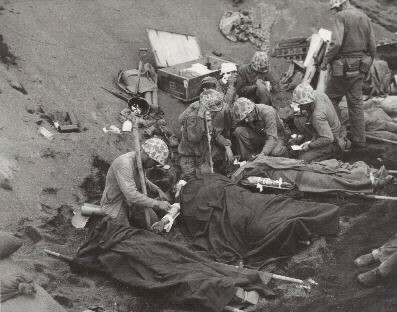 Iwo Jima Invasion, February 1945: Navy doctors and corpsmen administer to wounded marines at an Iwo Jima first aid station, 20 February 1945. Navy Chaplain, LtJG John H. Galbreath (right center) is kneeling beside a man who has severe flash burns, received in an artillery battery fifty yards or so away. Photgraphed by W.O. Obie Newcomb, Jr. USMCR. Naval History and Heritage Command Photgraphic Section #80-G-435702.