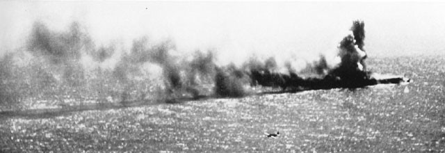 Two of our torpedo planes maneuver in for the kill as the heavily dive-bombed Shoho goes to destruction in smoke and flames.