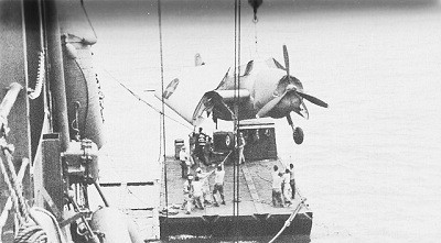 Image of U.S.S. Kitty Hawk at Pallikulo Bay, New Hebrides, unloading torpedo plane to self-propelled 50-ton barge.