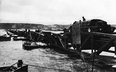 An Army DUKW Crosses One of the British-Built WHALE Bridges at OMAHA Beach.