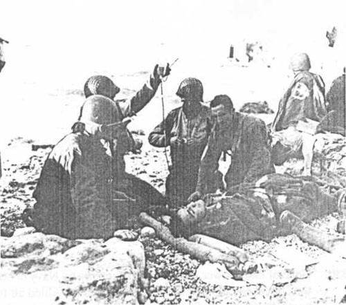 "Army ""medics"" treat a casualty on Fox Green beach. Heavy casualties to the assault troops would have been much higher but for DESRON 18 and other fire support ships."