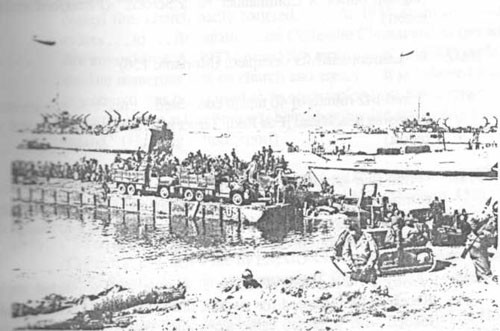 "Four days after D-Day, landing craft and a ""Rhino"" ferry pour troops and vehicles across the landing beaches. This massive buildup of strength during the early weeks of invasion tilted the balance toward the Allies and led to the eventual breakout from the beachhead."