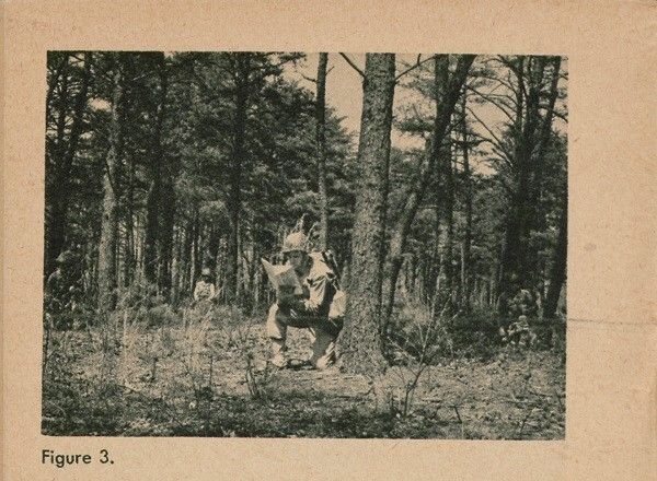 Figure 3: Soldier reading map in forest.