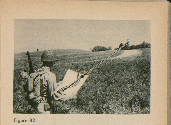 Figure 82: A man holding a map in a field with a doted line leading from the map to a water tower off in the distance.