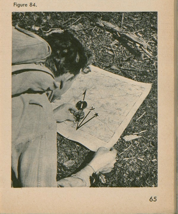 Figure 84: A man looking at map with a compass on top and a declination diagram.