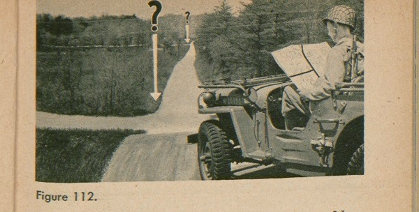 Figure 112: A soldier in a car looking at a map to determine direction.
