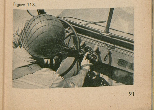 Figure 113: A soldier pointing at the mileage gauge in a jeep.