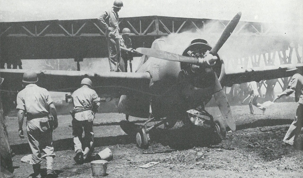 MARINE FIGHTER PLANES fell victim to many mishaps. This MAG-23 F4F-4 is being saved by bucket-brigade methods. Note bullet-pierced propeller blades.