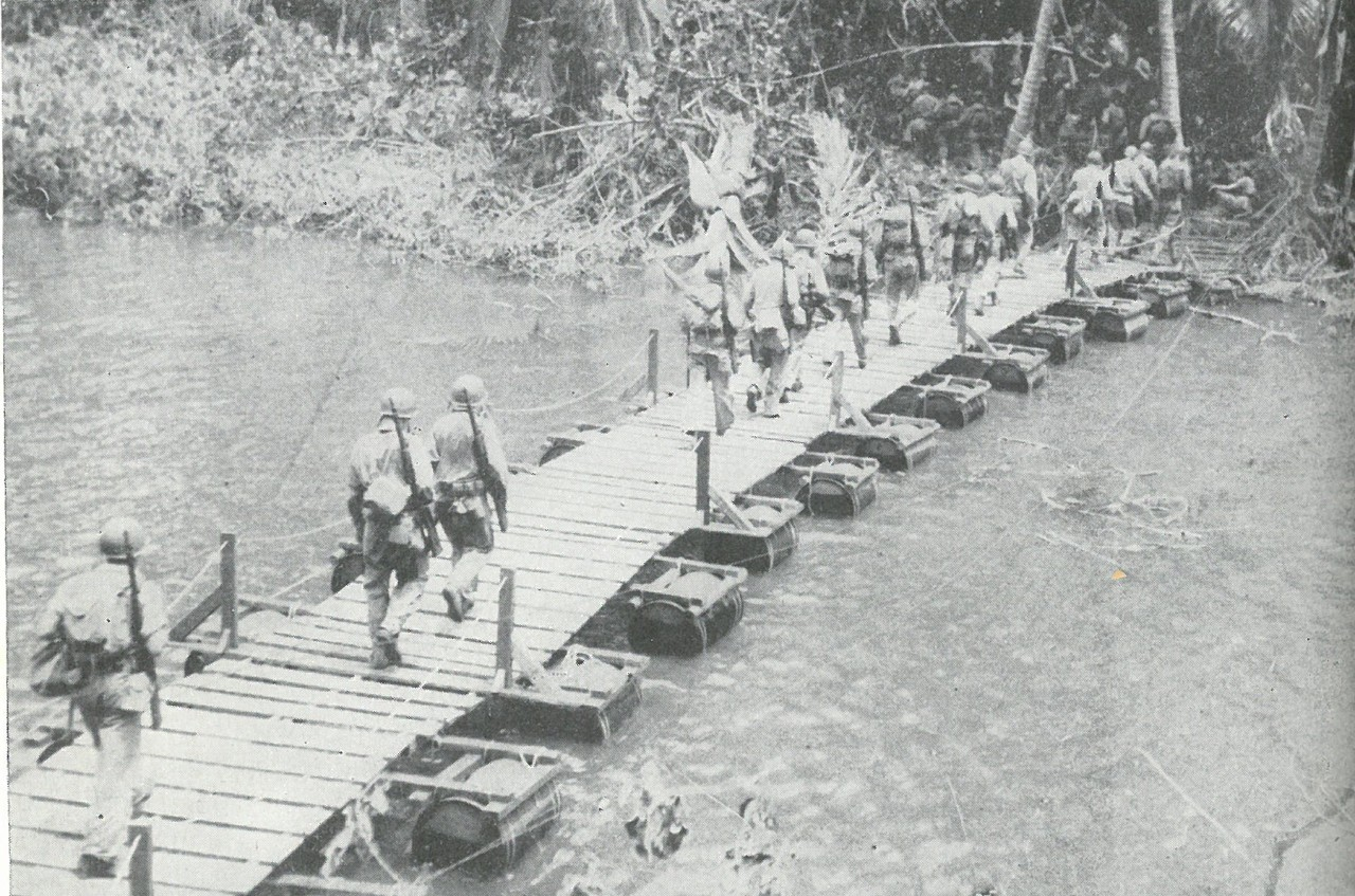 PATROLLING INTENSIFIED as it became evident that this was the only effective method of divining Japanese intentions under Guadalcanal jungle cover. This Marine unit is crossing the Matanikau River footbridge.
