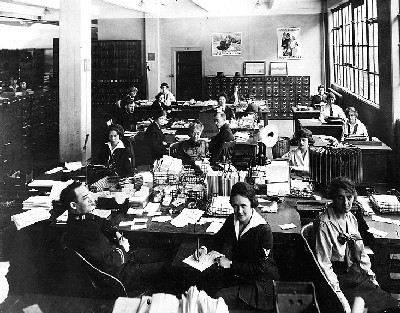 Navy Department, Washington, D.C. Military and civilian personnel in an office in the Main Navy or Munitions Buildings, circa 1919. Most of those present are Yeomen (F). A Medical Corps Lieutenant is seated in the front left center, dictating to a Yeoman (F). Note white shield around the mouthpiece of the telephone in the center of the photo; also wire document baskets on desks and Liberty Loan posters on the wall