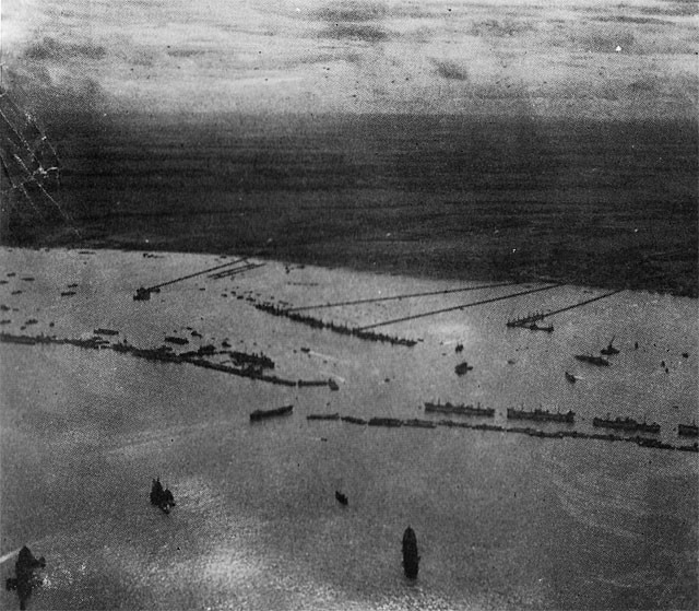 "Here is a general view of the ""MULBERRY"" harbor completed and in full operation. In front is the breakwater of caissons and blockships; to the center is the row of pierheads forming the wharf, and running from them to the shore are the floating roadways. All together they form a port about as big as Dover."