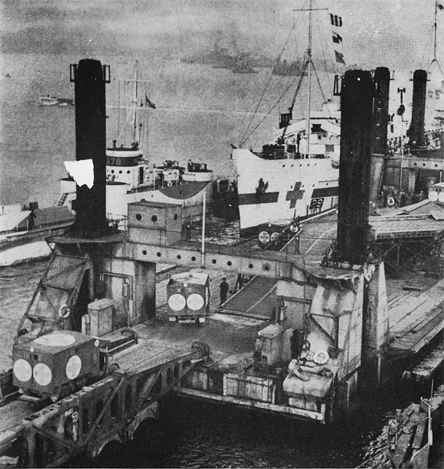 The pierhead in action. Wounded are being transferred from the ambulances to a hospital ship for return to England.