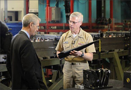Rear Adm. Matthew Klunder, chief of naval research, shows off a Hypervelocity Projectile (HVP) to CBS News reporter David Martin during an interview held at the Naval Research Laboratory's materials testing facility.