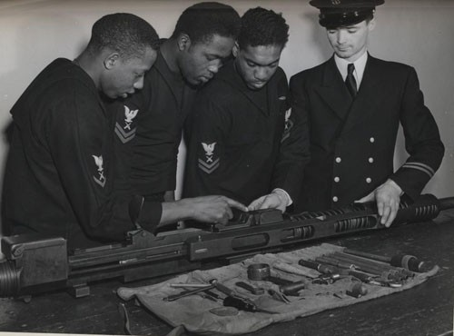 """Under the direction of Chief Gunner's Mate Rex Ashley, USN, three gunner's mates assemble and study a 20-mm. gun, the type which they will man aboard the DE [destroyer escort]. Trainees at Norfolk are (left to right) Albert A. Davis, Gunner's Mate Second Class, and Warrren Vincent, Gunner's Mate Second Class. [Only two gunner's mates are identified in caption.]"