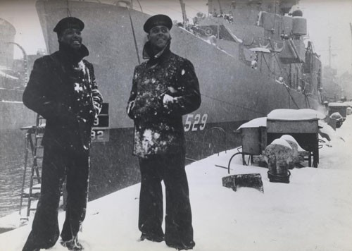 """'What's a little snow?' laugh two members of the predominantly Negro crew of the USS Mason as they stand proudly beside the bow of their new destroyer escort vessel, commissioned at Boston Navy Yard today. Eventually, the entire crew of this ship will be Negroes. [Released: First Naval District, 20 March 1944.]"