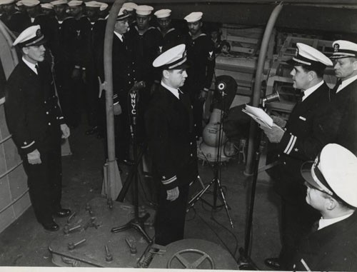 """'Subchaser manned by Negroes is commissioned at New York, 25 April 1944.' Lieutenant Eric Purdon, USNR, reads the orders directing him to assume command of the USS PC-1264, as officers and men of the ship's company stand at attention. The 173 foot sub hunter joins the naval service with 53 Negroes in her crew."""