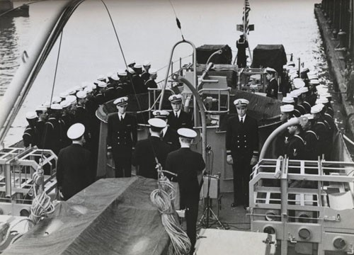 """'Subchaser manned by Negroes is commissioned at New York, 26 April 1944.' The national Ensign is raised on the USS PC-1264, and crew members stand at attention on the fantail as the commissioning ceremony is completed."""