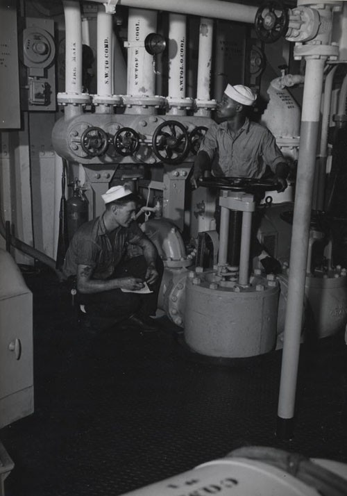 """Recording pressures in the engine room aboard this ship somewhere in the Pacific is Metalsmith Ben L. Dunn, Jr., while George Redd, Fireman Second Class, mans a valve as he keeps an eye on the gauge."""