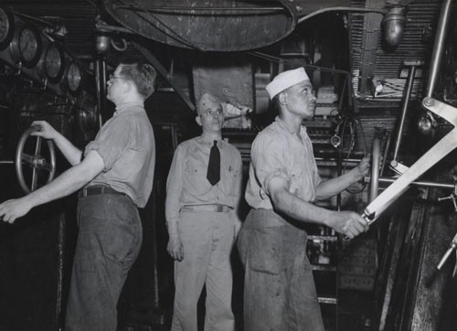 """Main engine throttles are handled aboard a large ship somewhere in the Pacific by Robert E. Beach, Machinist's Mate Second class, USNR, and Clarence Spears, Machinist's Mate Third Class, USNR. In the center is Chief Machinist's Gentry D. Keathley, Assistant engineering Officer. Machinist's Mate Spears stood third in his class at the machinist mate service school at Great Lakes, Illinois, and is doing an exceptionally good job aboard this ship according to Chief Keathley."""