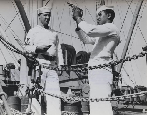 """Relieving the watch at the quarterdeck somewhere in the Pacific, Coxswain William Green observes safety precautions in checking his pistol while Albert S. Herbert, Quartermaster First Class, stands by with a clip of ammunition and holster belt, ready to complete the formalities."""