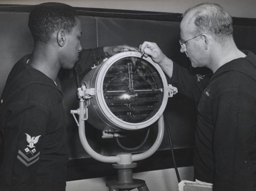 """The functions of the various parts of a 'blinker' are explained in detail by Signalman First Class Ernest V. Alderman, USNR, to Signalman Second Class Julius Holmes, who will be operating one aboard a DE [destroyer escort]."