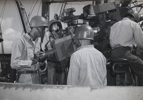 """Ready for action, this gun's crew includes a Negro Gunner's Mate striker who has been aboard this ship in the Pacific only a short time but is doing excellent work. He is Earl Jones, Seaman First Class, shown at the left. Others in the picture are Francis Devitis, Seaman First Class, Chief Gunner's Mate Clyde Scheuer, and Joseph Schiavo, Gunner's Mate Third Class."""