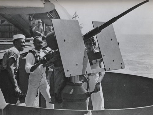 """Double duty - Negro mess attendants aboard US warships can serve out hot metal to the enemy as well as chow to US sailors. The cry 'battle stations' sends them to a 20mm gun aboard this fighting ship."""