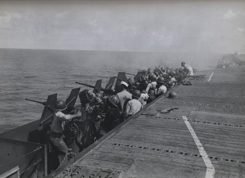 """'Negroes train sights on Japs at Saipan' - Under the direction of a gunnery officer, US Navy enlisted men pour lead at Jap planes attacking one of the aircraft carriers in the Navy Task Force raiding the Jap base of Saipan in the Marianas on 17 February 1944."""