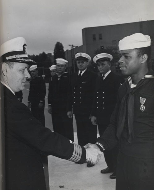 """Award of Purple Heart to William L. Parker, Steward's Mate Second Class, by Captain H. E. Schonland 'for wounds received in action against an enemy of the United States on 20 October 1944.'"""