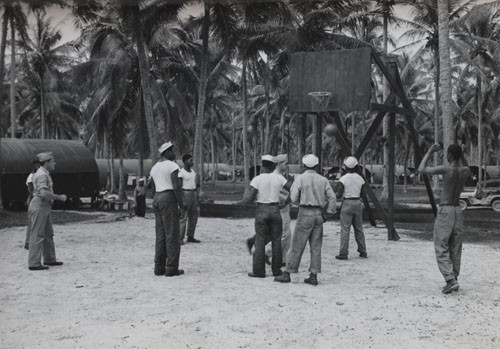 """'Recreation for Negro Seaman in South Pacific' - Full expression is allowed for recreational activities for Negro seamen stationed on Espiritu Santo in the New Hebrides. In their off-duty hours they play baseball, basketball, and other outdoor and indoor sports. Though far from home, their combined energies have made of the tropic base a palm-decorated 'home away from home' as they serve on the far-flung Pacific front. This photo shows one of the basketball teams in action."""