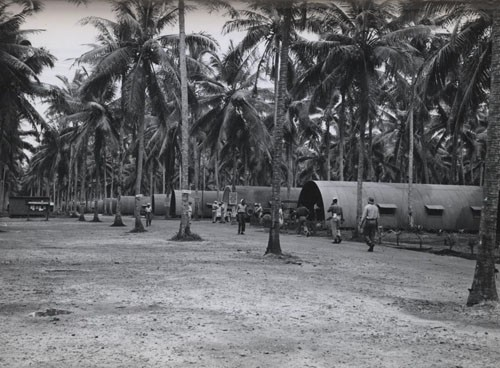 """'Among the Navy men in the New Hebrides' - Members of a navy base company of enlisted Negroes keep the wheels humming at a Navy Base on Espiritu Santo in the New Hebrides. Putting their varied talents into effect, they include within their ranks motor machinist's mates, boatswain's mates, signalmen and storekeepers. Photo shows Main street at Base Camp Annex. Back of bulletin board is the Mail Hut."""