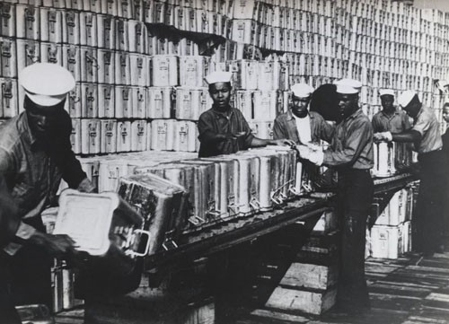"""Navy Negroes 'Pass the Ammunition.' - More than 6,000 Negro enlisted men are now serving in the Navy's ordnance station, performing their duties with an ability and zest which has qualified many for promotion. These youths passing 1.1 shell cans down a conveyor for stacking are assigned to St. Juliens Creek Naval Ammunition Depot. The duties that may be assigned to these enlisted men range from manual tasks to handling 'live' ammunition at the battlefronts. A number of the most skilled have been already sent overseas, and more will be sent out as replacement recruits fill the ranks at US bases."""