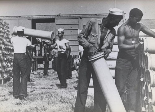 """'Negro enlisted men play ordnance 'Shell Game'.' - One of the unending tasks for enlisted men assigned to Naval Ordnance is the handling of empty cases in which shells are shipped. These colored Navy men at St. Juliens Creek Ammunition Depot in Virginia stack empties which held five-inch shells. The more than 6,000 Negro enlisted men in Navy Ordnance may be given any of the duties which fall to all enlisted men, ranging from manual tasks to hazardous assignments requiring great skill, such as handling live ammunition in a combat zone."""