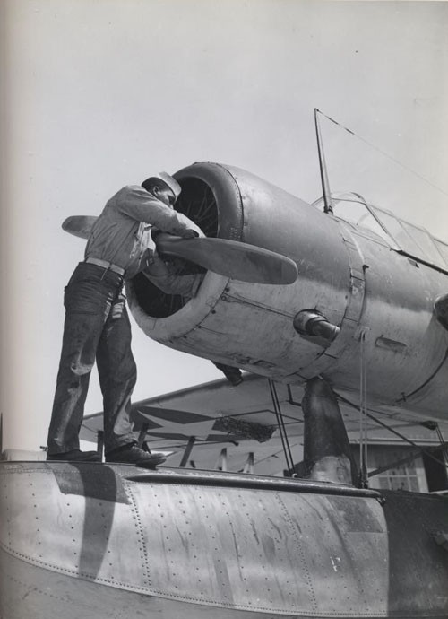 """Working on the motor of an OS-2-V, at US Naval Air Station, Seattle, Washington."""