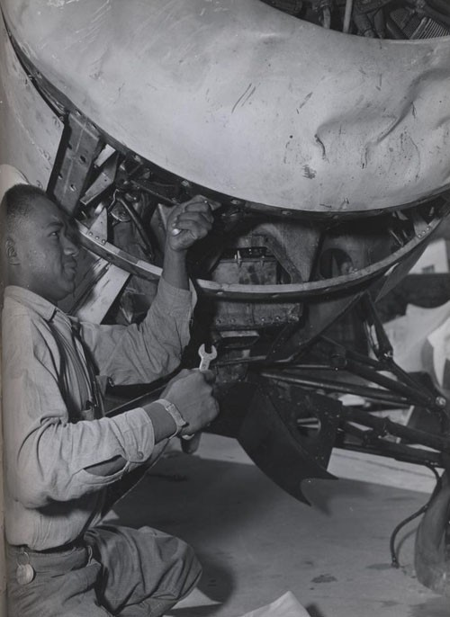 """Lattes Whitted, Seaman Second Class, helps to repair a damaged ship at the US Naval Air Station, Seattle, Washington."""