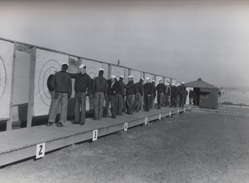 """Tabulation of scores of Naval Air Station Pasco, Washington sailors. Men pointing to targets are ordnance instructors."""
