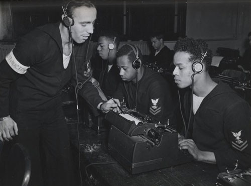 """Receiving and typing off messages, just as they'll be doing when the destroyer escort goes to sea, Radioman Second Class James W. Graham, (right), Radioman Second Class Wendell P. McMillan, and Radioman Third Class Alfred G. Mathis, get pointers at Norfolk NOB [Naval Operating Base] from instructor Radioman Second Class Charles G. Pelham, USN."